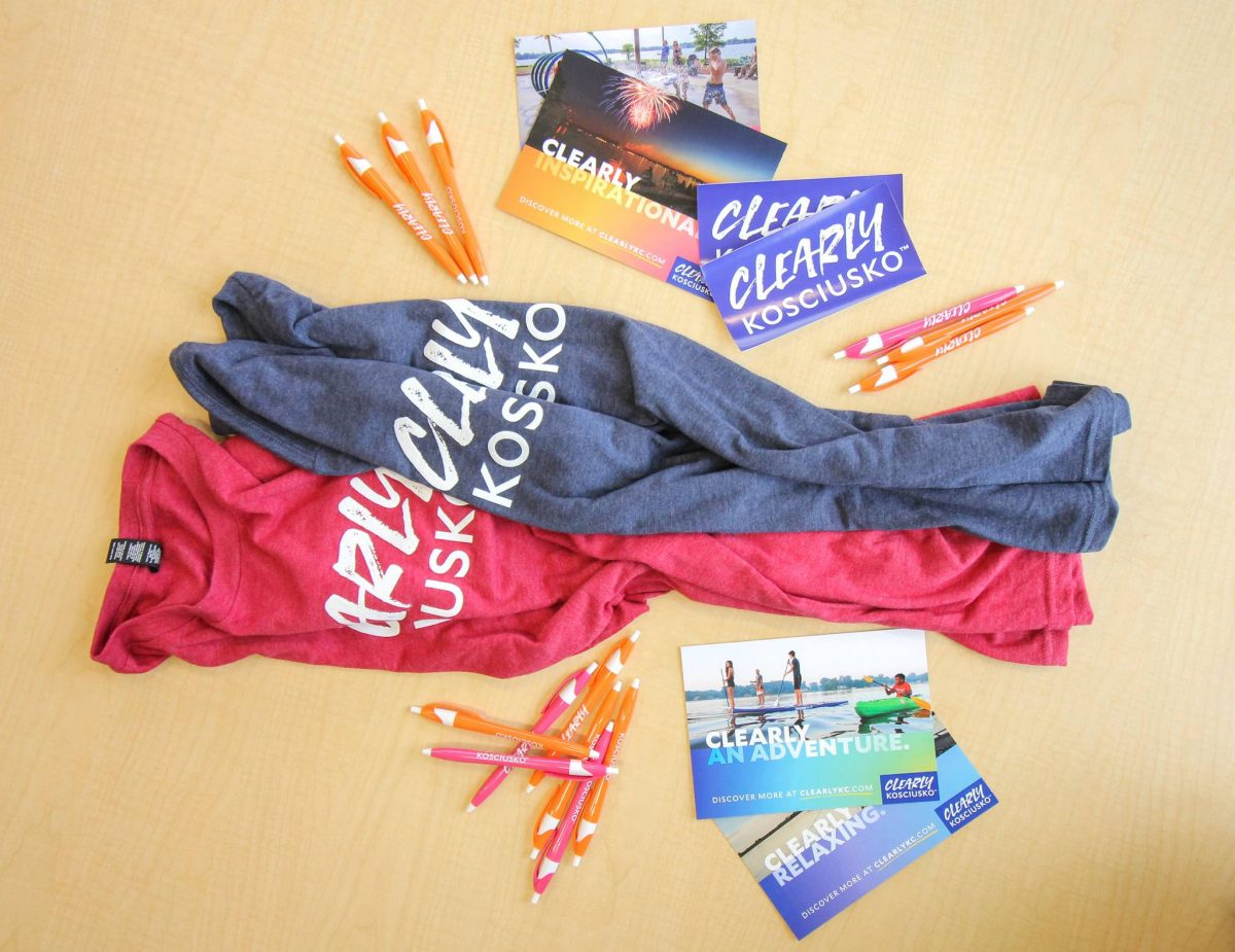 "alt=""Photo of Clearly Kosciusko t-shirts, stickers, pens, and postcards on a wooden table"""