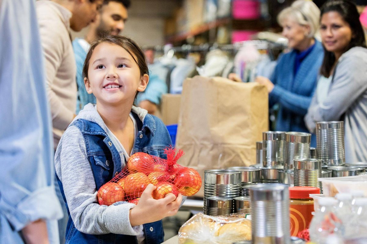 alt=child holding a bag of apples at a food bank table