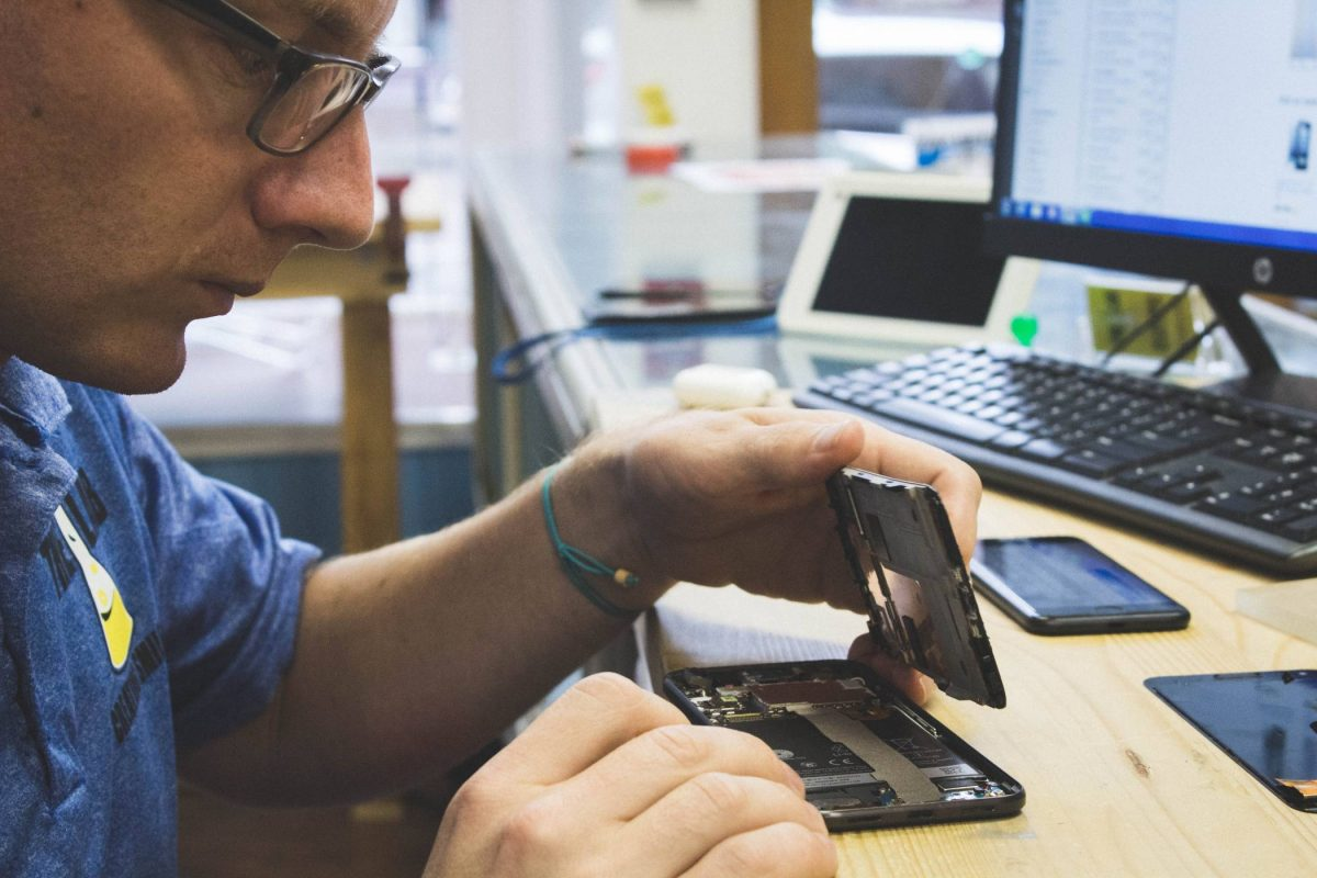 """alt=""""Lyle Shrock, owner of The Lab in Warsaw, IN, works to repair a broken cell phone at a desk"""""""